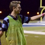 Senior Cody Luenz gestures towards a teammate on the field in anticipation. Photo by Abby Blake