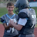 Freshmen Johnny Looney and Jack Ryan play with an ice pack on the sidelines. Photo by Abby Blake