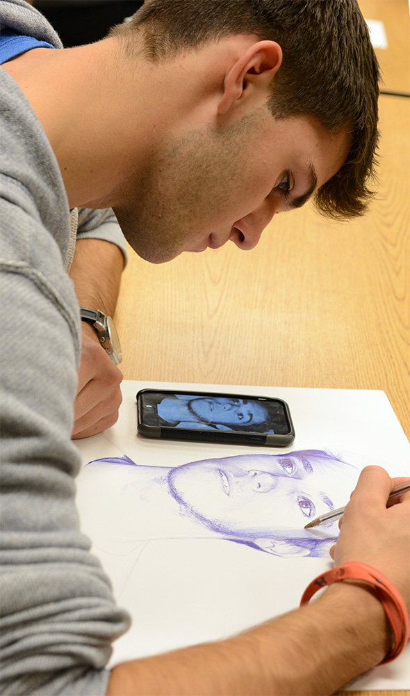 Senior Sam Engelken replicates a photo in his AP/IB Art during open work time after the class critique. Photo by Haley Bell