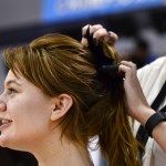 Cheer coach Mallory Gaunce ties a bow into senior cheerleader Maggie Brophy's hair before the game. Photo by Diana Percy