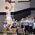 Junior Trevor Thompson shoots the ball while the Lancer Dancers and cheerleaders watch anxiously. Photo by Diana Percy