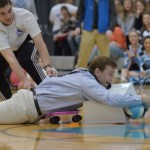 "During the life-sized ""Hungry Hippo"" game, junior Grayson Rapp pulls teammate, junior Eli McDonald across the floor in a fight to win. Photo by Abby Blake"