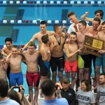 The boys swim and dive team poses on top of the podium with the State Championship trophy. Photo by Haley Bell