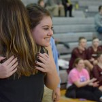 Senior Erin Staehr hugs cheer coach Mallory Gaunce before walking across the gymnasium during cheer senior night. Photo by Abby Blake