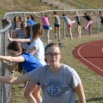Girls track warms up along the fence before practice. Photo by Audrey Kesler