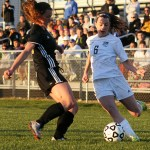 Freshman Izzy Rapp attempts to pass the ball to a teammate before her Shawnee Mission West defender takes possession. Photo by Haley Bell