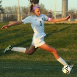 Senior Elizabeth Shook kicks the ball towards the goal to keep it from going out of bounds. Photo by Haley Bell