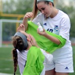 Junior Libby Legard helps Junior Ellie Booton put eyedrops in her eyes on the bench. Photo by Kaitlyn Stratman