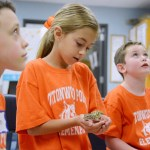 The two boys listen as Senior Emma Olander teaches them about the reptiles, while the girl holds the leopard gecko. Photo by Kaitlyn Stratman