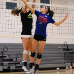Senior Emma Henderson and freshman Bridgid Went both jump up to hit the ball. Photo by Diana Percy