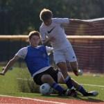 Senior Taylor Stover slides to intercept the ball from sophomore Cooper Holmes. Kaitlyn Stratman