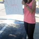 Junior Kelly Romer hollers at cars to go to the bake sale. Photo by Audrey Kesler