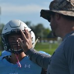 Freshman Kaden Bornholtz talks to coach Gagnon about tactics for tackling and blocking, beofre Bornholtz has to go back in the game. Photo by Morgan Plunkett
