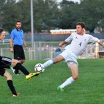 Senior Grayson Rapp kicks the ball and manages to keep it away from the opposing player. Photo by Katherine Odell