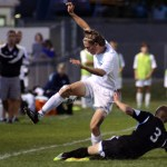 Senior Clayton Philips trips over a player who is sliding to kick the ball. Photo by Ellen Swanson