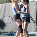Freshmen Ava Stechschulte and Elli Tucker high five each other after winning one game in their doubles match. Photo by Haley Bell