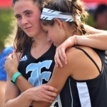 Junior Madeline Hlobik and sophomore Lucy Hoffman console each other after crossing the finish line. Photo by Libby Wilson