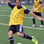 Freshman Hayden Talge kicks the soccer ball towards his teammates. Photo by Izzy Zanone