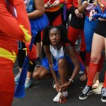 Senior Reami Boone takes a break to tie her shoes while walking with the senior float. Photo by Morgan Browning