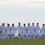 Boys' Varsity Soccer team steps onto the field holding hands while announcer calls players names. Photo by Ava Simonsen