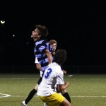 Senior Oliver Bihuniak jumps between two Olathe South players to head the ball.  Photo by Sophie Storbeck
