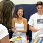 Seniors Emory Foster and Chace Prothe laugh as Prothe serves sausages to his sister, sophomore Paige Prothe. Photo by Ellie Thoma