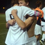 "Senior Clayton Phillips and senior Stanley Morantz hug after cheering with the east students. Phillips says, ""I feel like this couldn't have been a better way to win regionals, coming back from being down 2-0, winning off a free kick by Oliver in over time, against BVNW the team we have wanted revenge against our whole east careers, it was perfect."" Photo by Audrey Kesler"