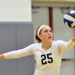 Junior Ally Huffman positions the volleyball before serving. Photo by Katherne Odell