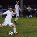 Senior Grayson Rapp shoots but the ball curves to the right of the goal. Photo by Kaitlyn Stratman