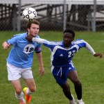 Sophomore Will Tulp tries to beat his opponent to the ball before it lands. Photo by Kaitlyn Stratman