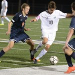 Senior Oliver Bihuniak dribbles the ball around two Olathe East players. Photo by Carson Holtgraves