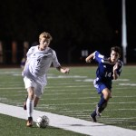 Junior Sam Thompson keeps possession of the ball while traveling down the field to score a goal. Photo by Katherine Odell