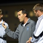 Varsity soccer coach Jamie Kelly talks to the players during halftime. Photo by Katherine Odell