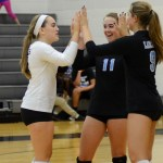 Juniors Ally Huffman, Victoria Yedo, and Syndey Ashner high five before starting their first game. Photo by Ellen Swanson