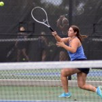 Junior Grace Chisholm returns the ball while warming up for her doubles match. Photo by Ellen Swanson