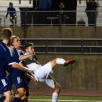 Senior Grayson Rapp gets pulled back as he kicks the ball to keep away from the defenders.  Photo by Annie Lomshek