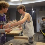 Sophomore, Abe Laughlin helps freshman, Peter Kohring with making his cutting board the right size. Photo by Grace Goldman