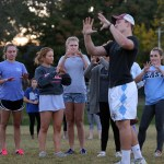 Holding up his hands to show, junior Milton Braasch teaches the girls how to catch a football. Photo by Kaitlyn Stratman