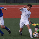 Freshman Joseph Wagner attempts to steal the ball from the Rockhurst goalie. Photo by Carson Holtgraves