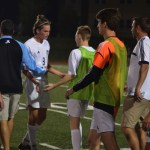 Senior Clayton Phillips walks off the field greeting his team with high fives. Photo by Izzy Zanone