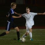 Senior Luke Ramey defends an attacker to disallow any goals. Photo by Audrey Kesler