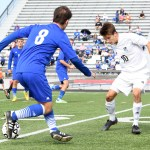 Senior Oliver Bihuniak challenges a Washburn Rural player for possession of the ball. Photo by Haley Bell