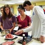 Freshman Evelyn Roesner, Addison Ferren and junior Alex Paris weigh the meat. Photo by Izzy Zanone