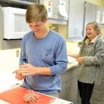 Junior Tom Phillips and Sophomore Kiki Ehrich laugh while making hamburgers. Photo by Izzy Zanone