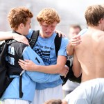 While the rest of the team says their goodbyes, senior Tommy Kerr hugs junior Tommy Nelson. Photo by Morgan Browning
