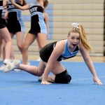 Sophomore Holly Frigon makes a face at the crowd after she falls during the routine. Photo by Maddie Smiley