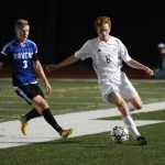 Junior Tommy Nelson steals the ball away from an Olathe defender. Photo by Ellie Thoma