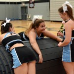 Sophomore Elle Angelo, Senior Elyse Chinnock, and Senior Tyler Lockton joke around as they roll up the mats after the routine. Photo by Ellie Thoma