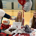 Seniors Ally Offerdahl and Sara Maddox receive a congratulatory handshake from head athletic director Debbie Kratzfey. Offerdahl will be attending University of Central Missouri for volleyball, and Maddox will be attending Mississippi State University for volleyball as well.  Photo by Ellie Thoma