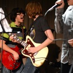 """Junior Andrew Carter jams out on his guitar with his band mate while performing """"Ain't No Rest for the Wicked"""" by Cage the Elephant. Photo by Ellie Thoma"""
